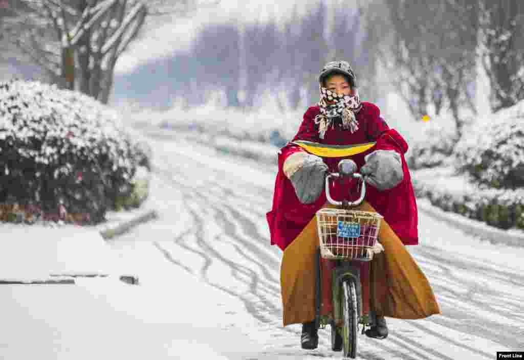 A woman rides her electric bicycle along a street during snowfall in Lianyungang, Jiangsu province, China.