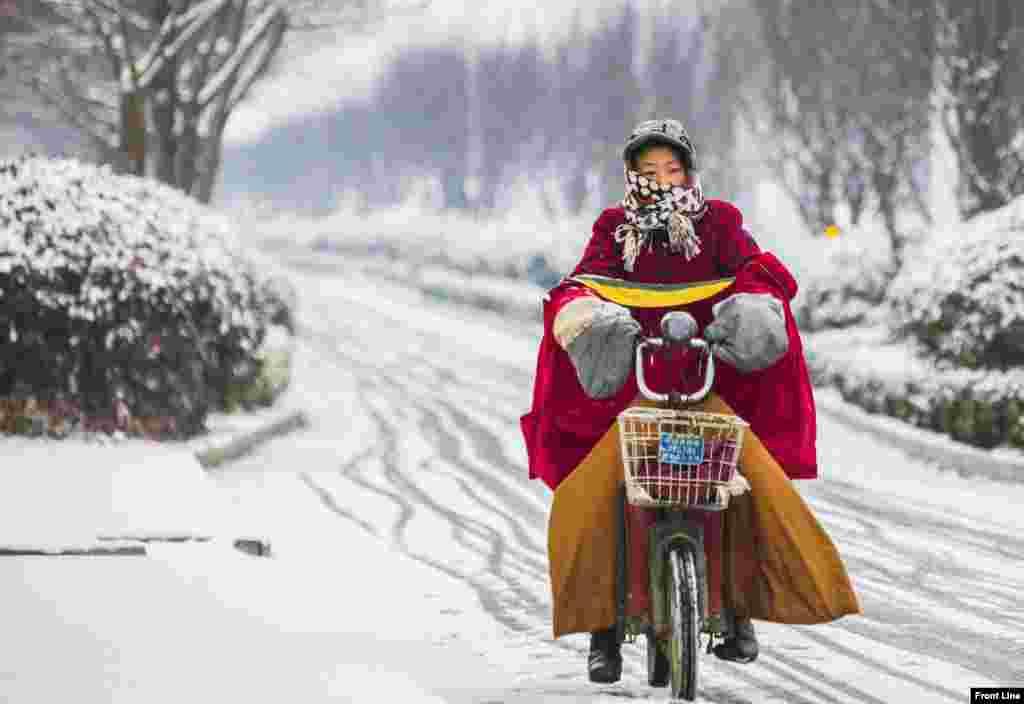 A woman rides her electric bicycle along a street during snowfall in Lianyungang, Jiangsu province, China.