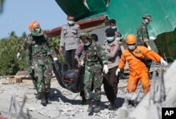 Rescuers carry the body of an earthquake victim recovered from debris of a collapsed mosque in Lombok, Indonesia, Aug. 7, 2018.