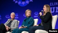 FILE - Former president Bill Clinton (L) and former secretary of state and Democratic presidential candidate Hillary Clinton (C) listen to their daughter and vice chair of the Clinton Foundation Chelsea Clinton during an event sponsored by the foundation in Tempe, Arizona, March 22, 2014.