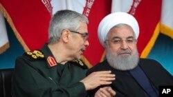 TT Iran Hassan Rouhani, bên phải, lắng nghe Tướng Mohammad Hossein Benghari, Chủ tịch ban Tham mưu trưởng các Lực lượng Iran, trong một cuộc diễu hành quân sự vào ngày 18/4/2019. (Iranian Presidency Office via AP)