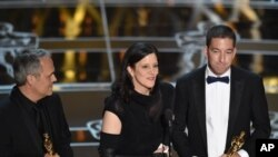"Dirk Wilutzky, from left, Laura Poitras and Glenn Greenwald accept the award for best documentary feature for ""Citizenfour"" at the Oscars on Sunday, Feb. 22, 2015, at the Dolby Theatre in Los Angeles. (Photo by John Shearer/Invision/AP)"