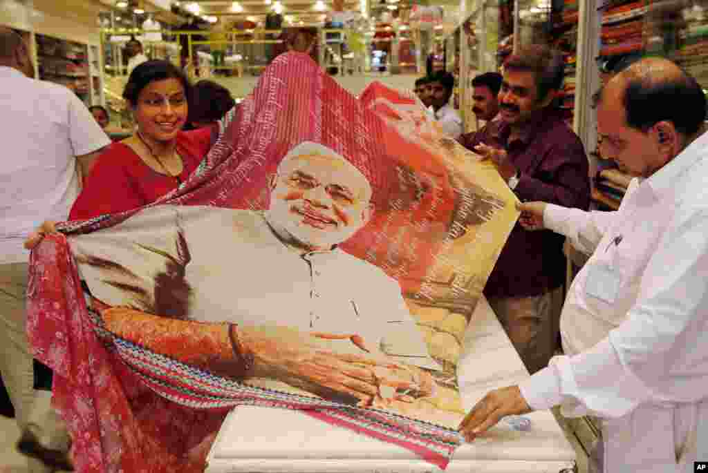 A woman holds a sari printed with a portrait of Bharatiya Janata Party's prime ministerial candidate Narendra Modi at a garments shop in Mumbai, May 14, 2014.
