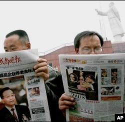Des Chinois lisant les comptes rendus de la visite du président Hu aux Etats-Unis