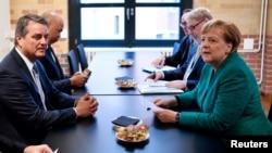 El jefe de la OMC, Roberto Azevedo y la canciller alemana, Angela Merkel, sostienen un encuentro al margen de una conferencia organizada por la Federación de Industrias Alemanas, en Berlin.