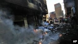 Egyptians gather next to a building belonging to Christians that was set on fire during clashes between Muslims and Christians in the Imbaba neighborhood of Cairo, May 8, 2011