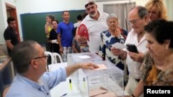 FILE - A man prepares to vote in Spain's general election at a polling station in Rincon de la Victoria, June 26, 2016.