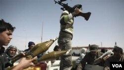 Soldados que desertaron de las fuerzas de Gadhafi y opositores celebran el haber recuperado el control de la ciudad portuaria y petrolera de Brega, en Libia.