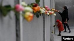2014年11月9日柏林墙倒塌25周年: 母亲和女儿在贝尔瑙尔大街柏林墙纪念馆献上玫瑰