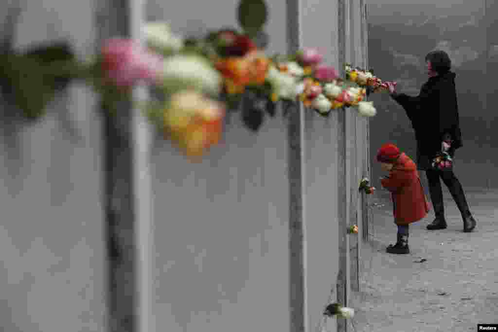 A mother and young daughter place roses at the Berlin Wall memorial in Bernauer Strasse, during a ceremony marking the 25th anniversary of the fall of the Berlin Wall in Berlin, Nov. 9, 2014.