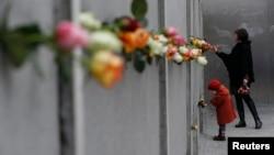 2014年11月9日,德国柏林举行柏林墙倒塌25周年纪念仪式。图为一对母女把玫瑰花放在在柏林墙上。