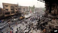 Pasukan keamanan Irak dan warga berkumpul di lokasi, pasca serangan bom terhadap pusat perbelanjaan di distrik Karada di Baghdad, Minggu (3/7).