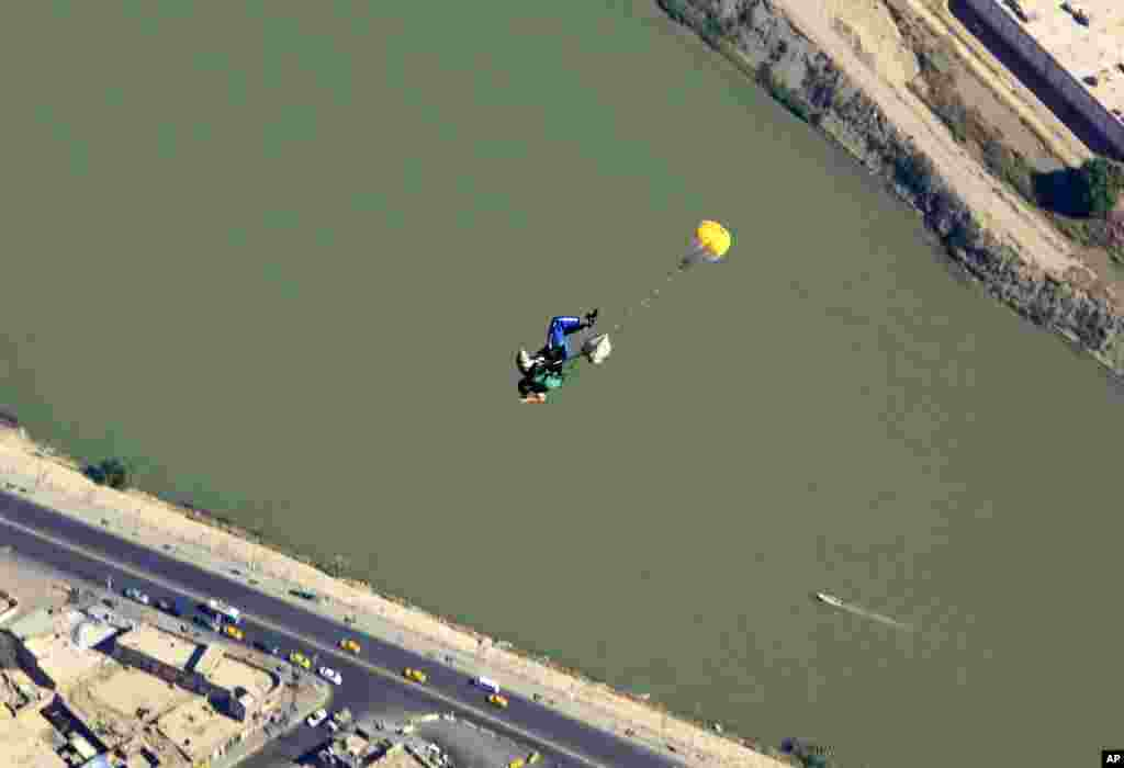 With the Tigris River beneath him, a member of Iraq's national skydiving national team parachutes over the capital during a training session in Baghdad, Friday, Sept. 27, 2013.