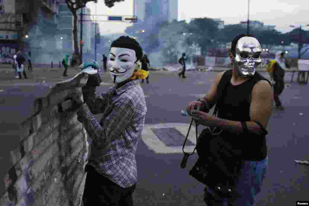 Anti-government demonstrators wearing masks hold a makeshift shield during clashes with police at Altamira square in Caracas, Feb. 27, 2014.
