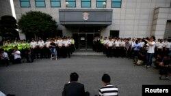 Anggota keluarga korban yang selamat dari bencana feri Sewol duduk di depan sebuah gedung tempat kru ditahan, setelah menghadiri kesaksian di pengadilan lokal di Gwangju, 10 Juni 2014.
