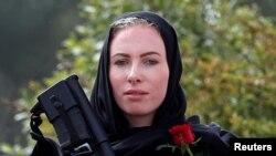 Yangi Zelandiyada oq tanli politsiyachi ayol boshida ro'mol, ko'ksida qizil atirgul bilan musulmon jamoasiga hamdardligini bildirmoqda