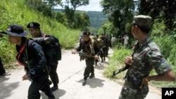 کمبوڈیا کا ایک فوجی (دائیں جانب) تھائی فوجیوں کو سرحدی علاقے میں واقع مندر کی جانب جاتے دیکھ رہا ہے۔ (فائل فوٹو)