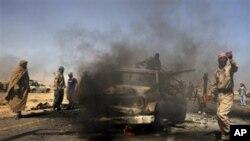 Des rebelles libyens inspectent deux véhicules de l'armée gouvernementale détruits par l'aviation de l'OTAN