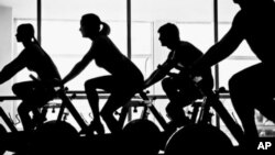 FILE - People are seen exercising on stationary bicycles.