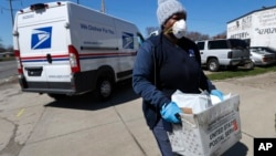 A United States postal worker outfitted with gloves and a mask makes a delivery in Warren, Michigan, April 2, 2020. The U.S. Postal Service has suspended mail to 22 countries due to the COVID-19 pandemic.