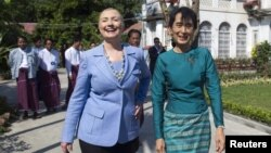 U.S. Secretary of State Hillary Clinton (L) and Myanmar's pro-democracy leader Aung San Suu Kyi tour the grounds after their meeting at Suu Kyi's house in Yangon December 2, 2011.