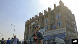 Afghan policeman stand guard after a battle with insurgents who took over a building in Kabul, Afghanistan, April 16, 2012.