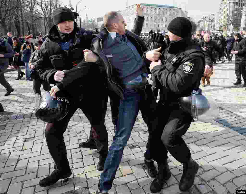 A counter-demonstrator is detained by riot police as activists take part in a rally for gender equality and against violence towards women on International Women's Day in Kiev, Ukraine, March 8, 2019.