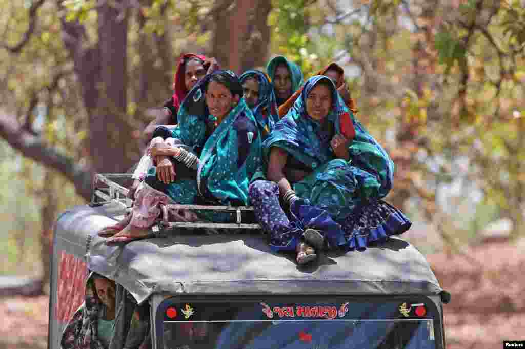 Women ride on top of a vehicle after casting their votes at a polling station in Sirohi district, Rajasthan, India.