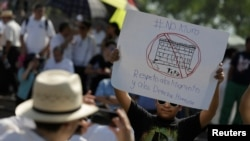 "A demonstrator holds a placard reading: ""No wall. Respect to immigrants and human rights"" during a protest against U.S. President Donald Trump's proposed border wall and to call for unity, in Monterrey, Mexico, February 12, 2017."