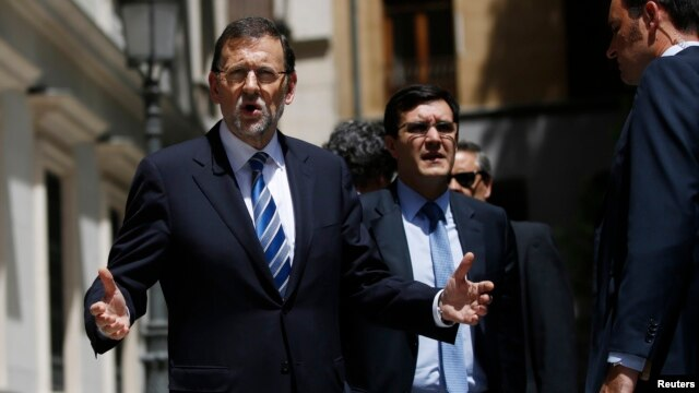 Spain's Prime Minister Mariano Rajoy (L) reacts to a question from a reporter as he leaves after a session at the Senate in Madrid, Aug. 1, 2013.