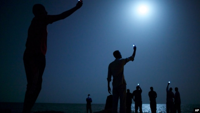In this photo provided on Feb. 14, 2014 by World Press Photo, the World Press Photo of the Year 2013 by John Stanmeyer, USA, VII for National Geographic, shows African migrants on the shore of Djibouti city at night, raising their phones in an attempt to  capture an inexpensive signal from neighboring Somalia in Djibouti City, Djibouti.