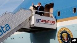 El presidente de EE.UU., Donald Trump, saluda al descender del Air Force One en el aeropuerto internacional de Zurich, Suiza, el jueves, 25 de enero de 2018.