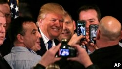 Ứng cử viên tổng thống của đảng Cộng hòa, doanh nhân Donald Trump mỉm cười khi chụp ảnh với những người ủng hộ sau khi được thông qua tại một cuộc họp công đoàn cảnh sát khu vực tại Portsmouth, New Hampshire, thứ Năm ngày 10/12/2015.
