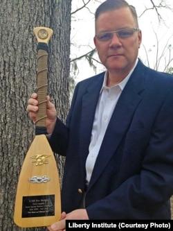 默德牧师手持军方颁发的奖章 (照片来源:Liberty Institute)