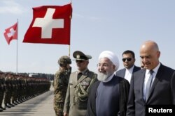 Swiss Federal President Alain Berset welcomes Iranian President Hassan Rouhani during Rouhani's official visit to Switzerland at the Zurich airport in Kloten, Switzerland, July 2, 2018.