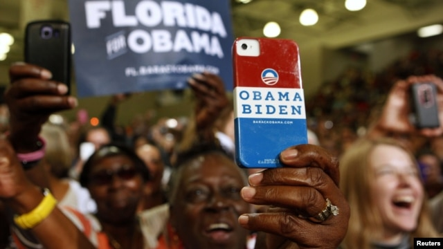 A supporter uses her personalized mobile phone to take a picture of U.S. President Barack Obama as he speaks at a campaign event at the Florida Institute of Technology in Melbourne, Florida, September 9, 2012.