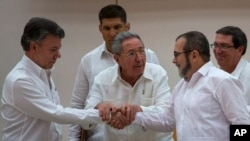 "Cuba's President Raul Castro, center, encourages Colombian President Juan Manuel Santos, left, and Commander the Revolutionary Armed Forces of Colombia or FARC, Timoleon Jimenez, known as ""Timochenko,"" to shake hands, in Havana, Cuba, Sept. 23, 2015."