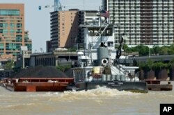 FILE - A tugboat pushes a barge loaded with coal up the Ohio River, past downtown Louisville, Kentucky.