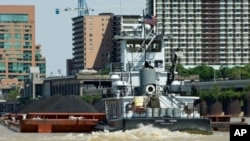 A small, but mighty, tugboat pushes a barge loaded with coal up the Ohio River, past downtown Louisville, Kentucky.