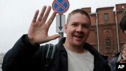 一名英國的綠色和平活動人士安東尼·佩雷特獲釋放後向媒體揮手.