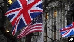 Pendukung Brexit memegang bendera Inggris dan AS di London, Jumat, 31 Januari 2020. (Foto: AP)