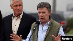 Colombia's President Juan Manuel Santos speaks while flanked by U.S. Defense Secretary Chuck Hagel (L) after a meeting at the military airport in Bogota October 10, 2014. Hagel began a trip to Latin America on Thursday, and will be visiting Colombia, Peru