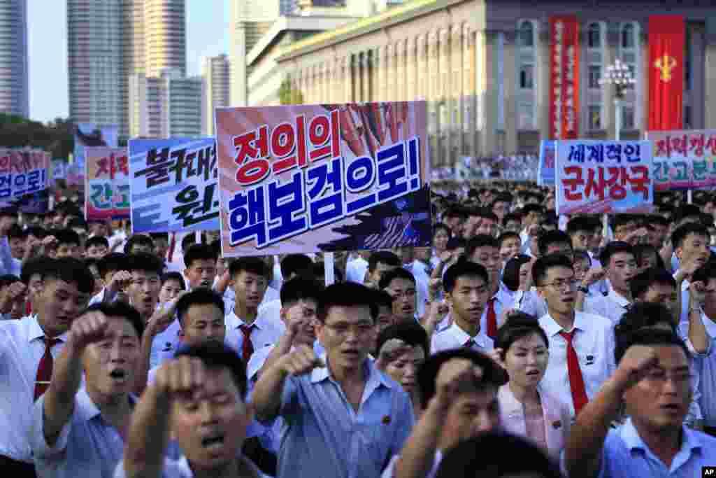 평양시 군중집회에서 참가자들이 '정의의 핵보검으로!' '세계적인 군사강국' 등 구호가 적힌 플랜카드를 들고 행진하고 있다.