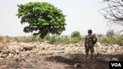 Un soldat se tient au milieu des ruines àChibok, Nigeria, le 25 mars 2016. (VOA/Chris Stein)