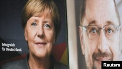 FILE - Election posters of German Chancellor Angela Merkel of the Christian Democratic Party (CDU) and Social Democratic Party (SPD) leader and top candidate Martin Schulz are seen in Hamburg, Germany, Sept. 24, 2017.