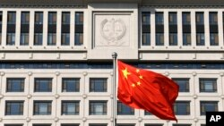 FILE - A Chinese national flag billows in front of Shandong Province Supreme People's Court in Jinan, eastern China, Oct. 24, 2013. Activists are calling on U.S. officials to put more focus on human rights in bilateral talks with China.