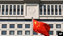 FILE - A Chinese national flag billows in front of a building of Shandong Province Supreme People's Court in Jinan.