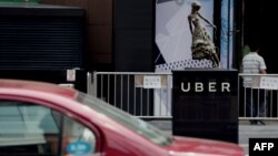 A taxi passes by an Uber station outside a shopping mall in Beijing. Uber is planning on bringing its UberEats to 22 more cities, but it's unclear if Beijing is among them.