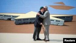 Ένας βετεράνος των συμμαχικών δυνάμεων και ένας των γερμανικών δυνάμεων αγκαλιασμένοι στην ακτή της Νορμανδίας, 70 χρόνια μετά την Απόβαση των Συμμάχων