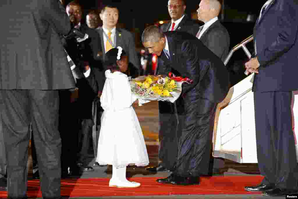 U.S. President Barack Obama receives flowers from an eight-year-old girl as he arrives aboard Air Force One at Jomo Kenyatta International Airport in Nairobi. Obama flew into Kenya late on Friday for his first presidential visit to his father's homeland, aiming to boost trade and security ties in East Africa.